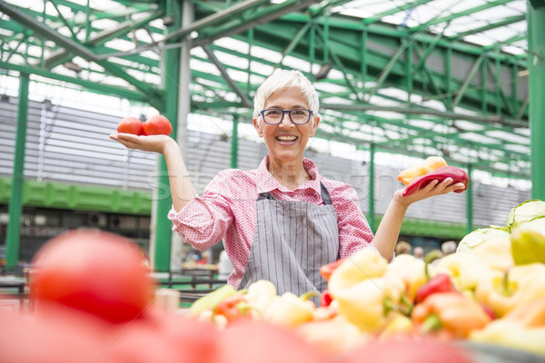 Good-looking senior woman wearing glasses sells  pepper on marke Stock photo © boggy