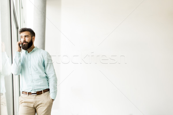 Handsome young man in formalwear talking on the mobile phone Stock photo © boggy