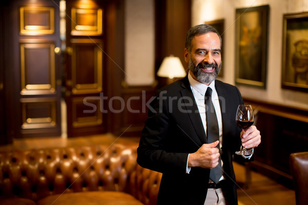 Handsome elegant businessman drinking red wine Stock photo © boggy