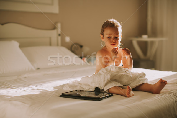 Sweet curly little girl with a towel over her wet body siting in Stock photo © boggy