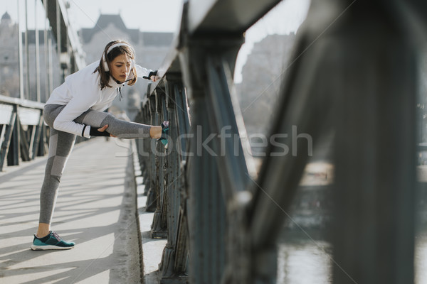 Young sportswoman stretching and preparing to run Stock photo © boggy