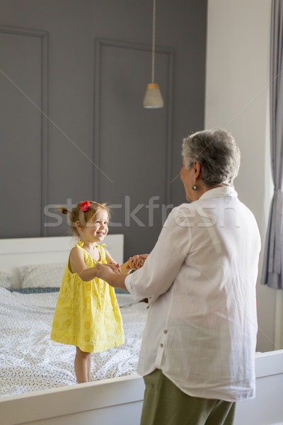 Grandma plays with a little granddaughter  on the bed Stock photo © boggy