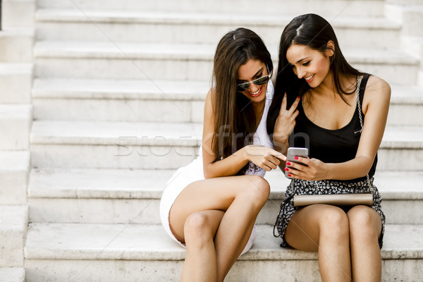 Stock photo: Two young women sitting on the stone steps outside and looking a