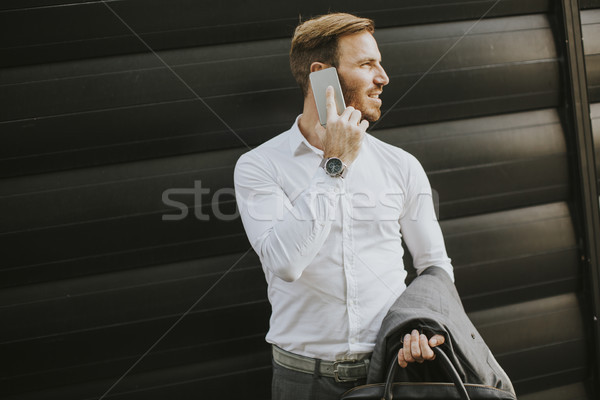 Young successful men entrepreneur using mobile phone outdoor Stock photo © boggy