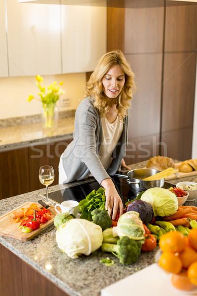 Fiatal nő áll tűzhely konyha mosoly otthon Stock fotó © boggy