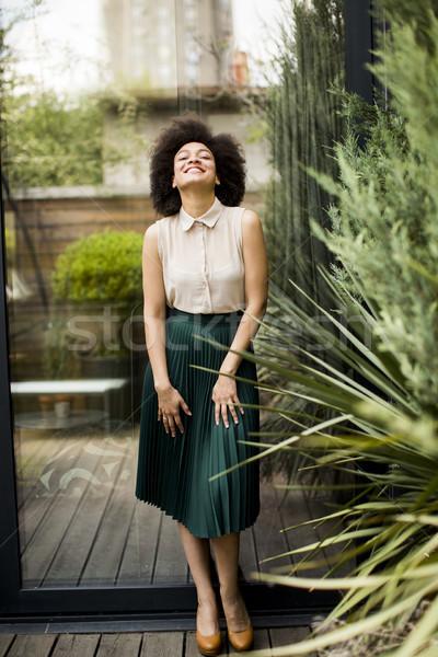 Mulher jovem cabelos cacheados verde saia posando ao ar livre Foto stock © boggy