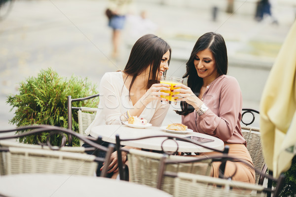 Portrait of beautiful young women eating cake at outdoors cafe Stock photo © boggy