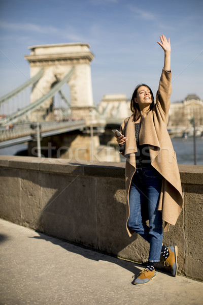Young woman holding mobile phone with Chain bridge in background Stock photo © boggy