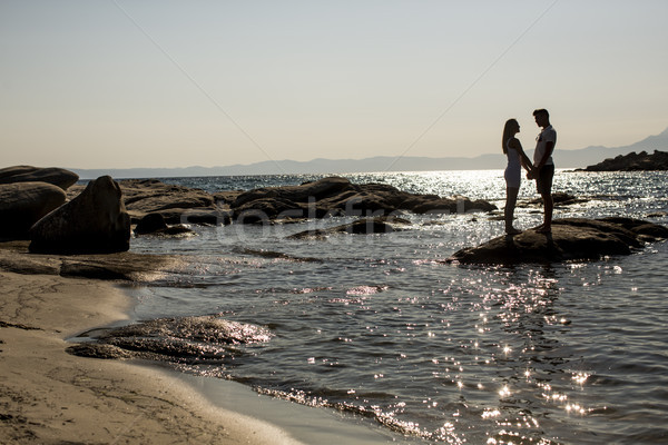Loving couple standing in the sea at sunset Stock photo © boggy