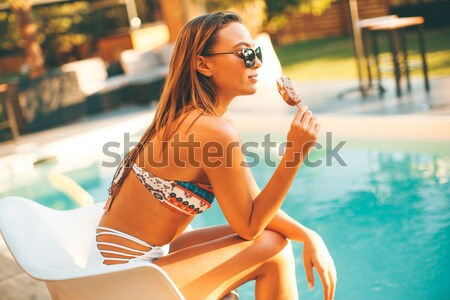 Pretty young woman with ice cream on the poolside Stock photo © boggy