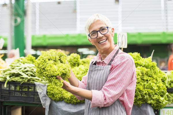 Senior woman sells lettuce on marketplace Stock photo © boggy