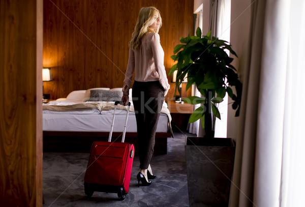 Jovem empresária quarto de hotel vermelho mala loiro Foto stock © boggy