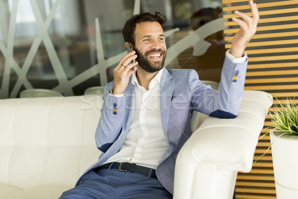 Empresario teléfono móvil jóvenes hombre de negocios sesión oficina Foto stock © boggy