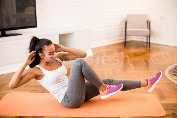 Stock photo: Young woman doing abs exercise in the room