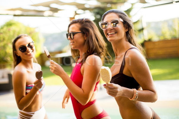 Pretty young women with ice creams by the swimming pool Stock photo © boggy