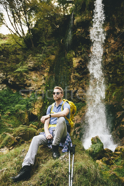 Young hiker stopped beside a mountain waterfall to rest Stock photo © boggy