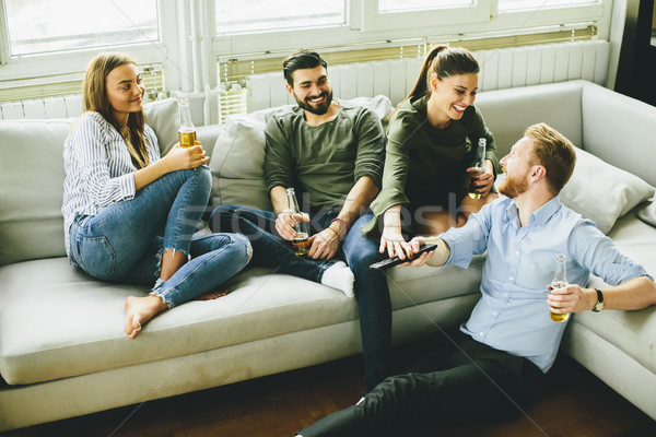 Friends watching TV , drinking cider and having fun in the room Stock photo © boggy