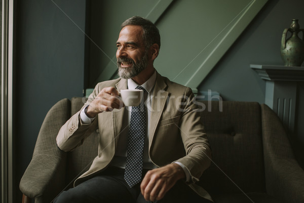 Handsome senior businessman drinking coffee in lobby Stock photo © boggy