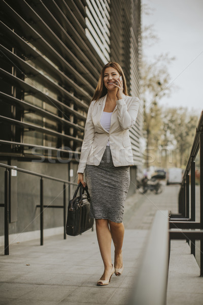 Businesswoman talking on the phone near office building Stock photo © boggy