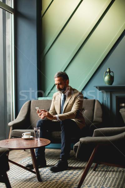 бизнесмен питьевой кофе мобильного телефона мнение Сток-фото © boggy