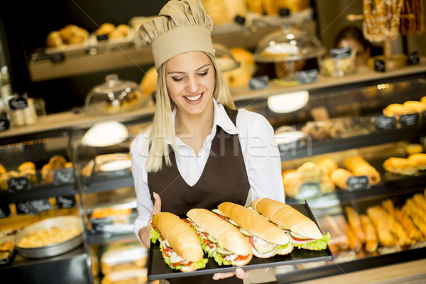 Beautiful female bakery posing with various types of sandwiches  Stock photo © boggy