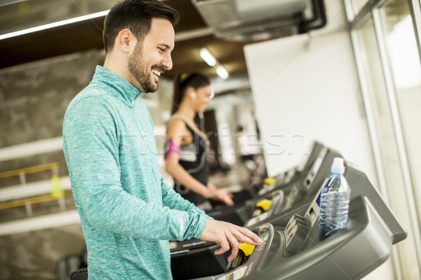 Young woman and man at the gym exercising and run on a treadmill Stock photo © boggy
