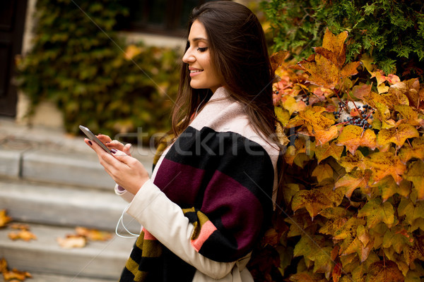 View at pretty young woman outdoor with mobile phone Stock photo © boggy