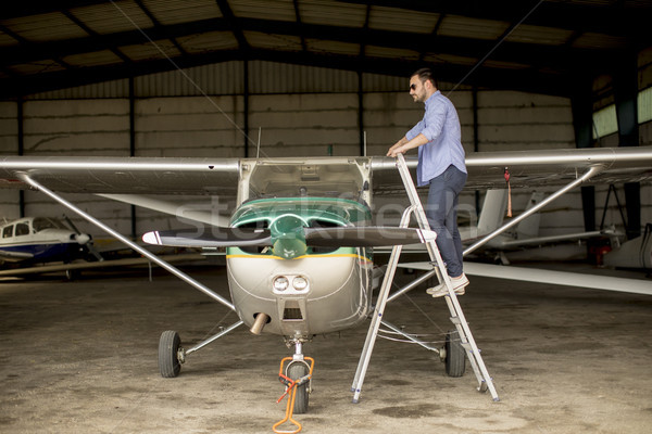 Young pilot checking airplane in the hangar Stock photo © boggy