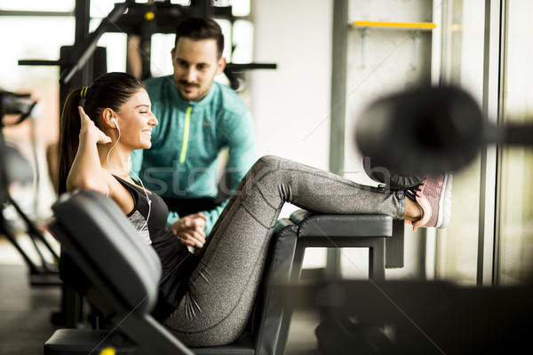 Vrouw oefening gymnasium helpen personal trainer jonge vrouw Stockfoto © boggy