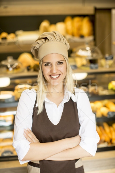 Stock photo: Beautiful young woman smiling confidently posing in her baker sh