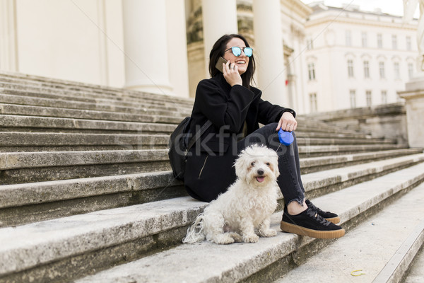 Young woman sitting on the steps with  small dog and using a mob Stock photo © boggy