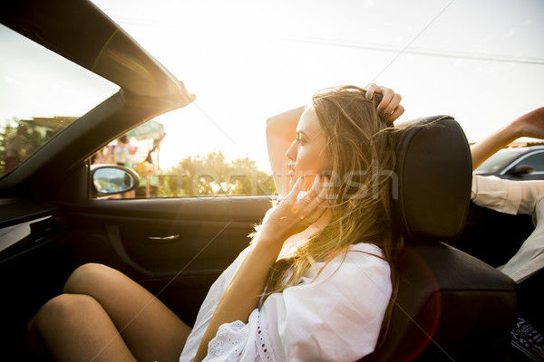 Woman uses mobile phone and siting in cabriolet at summer day Stock photo © boggy