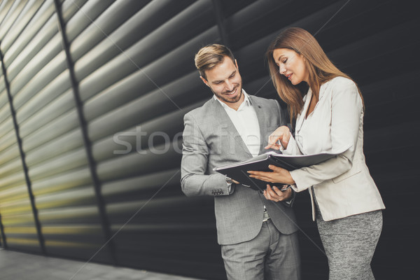 Young business people talking and viewing documents outdoor Stock photo © boggy