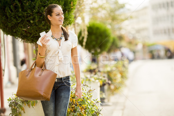 Fashionable brunette woman with handbag walking in the street Stock photo © boggy