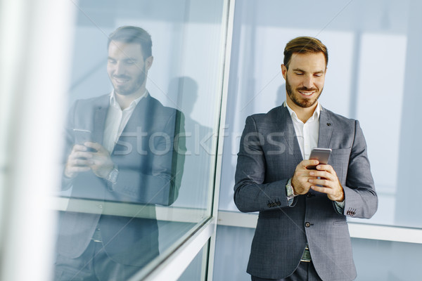 Stock photo: Happy smiling urban businessman using smart phone outside