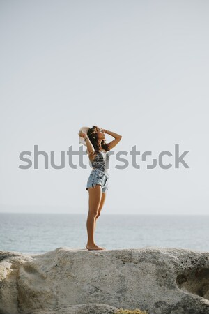 Pretty young woman on the stony shore Stock photo © boggy