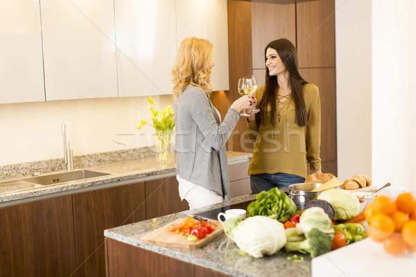 Kettő fiatal nők pirít fehérbor modern konyha Stock fotó © boggy