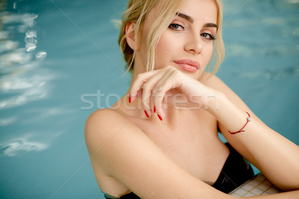 Pretty young woman relaxing on the poolside Stock photo © boggy