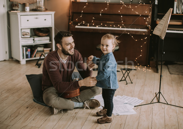 Young father and little daughter playing acoustic guitar Stock photo © boggy