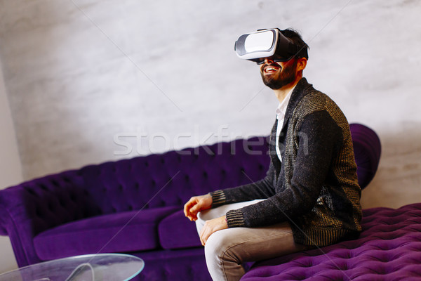 Bearded young man wearing virtual reality goggles in modern room Stock photo © boggy