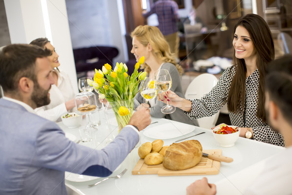 Stock photo: Young friends having dinner at home and toasting with white wine