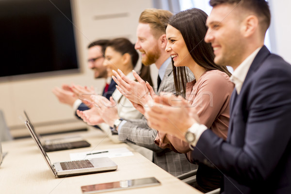 Happy smiling business team clapping hands Stock photo © boggy