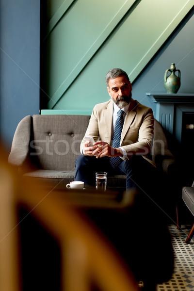 Bonito homem maduro telefone móvel relaxante sessão relaxar Foto stock © boggy