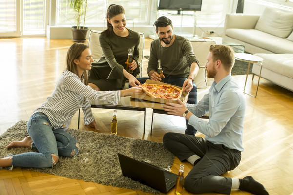 Young people eating pizza, drinking cider and have fun the room Stock photo © boggy