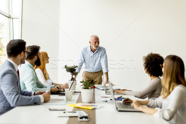 Senior boss holds a meeting for younger colleagues Stock photo © boggy