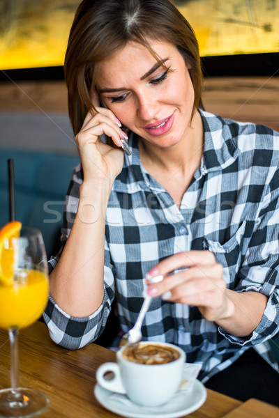 Beautiful young woman using cell telephone while enjoying her fr Stock photo © boggy