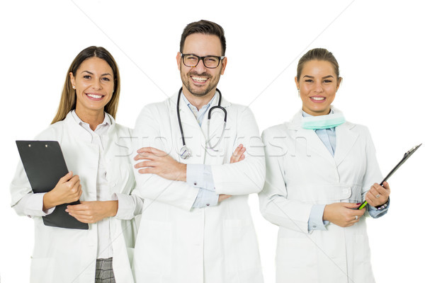 Portrait of three happy doctors who stand and smiling Stock photo © boggy