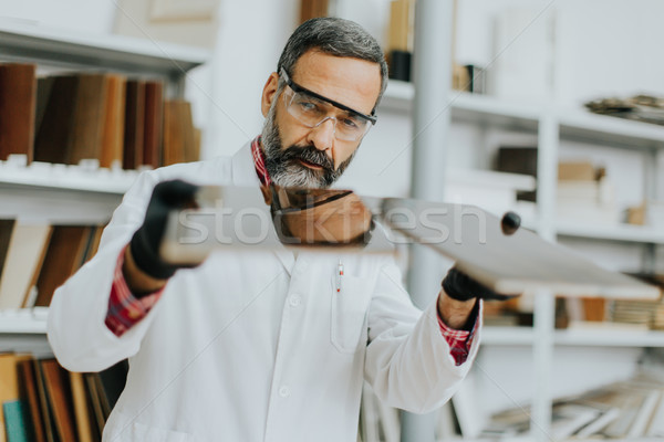 Handsome mature engineer testing colors on wooden specimens Stock photo © boggy