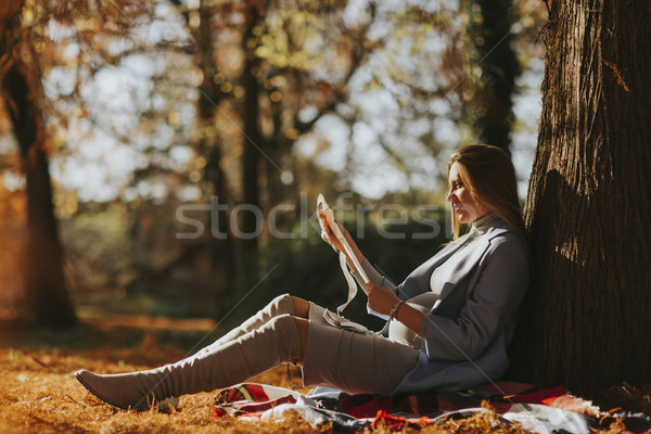 Young pregnant woman looking fetus ultrasound images in the park Stock photo © boggy