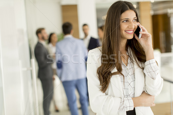Businesswoman on phone call with colleagues in background at off Stock photo © boggy